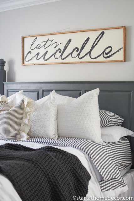 Throw pillows, a charcoal afghan and a lets cuddle sign are the perfect accessories.